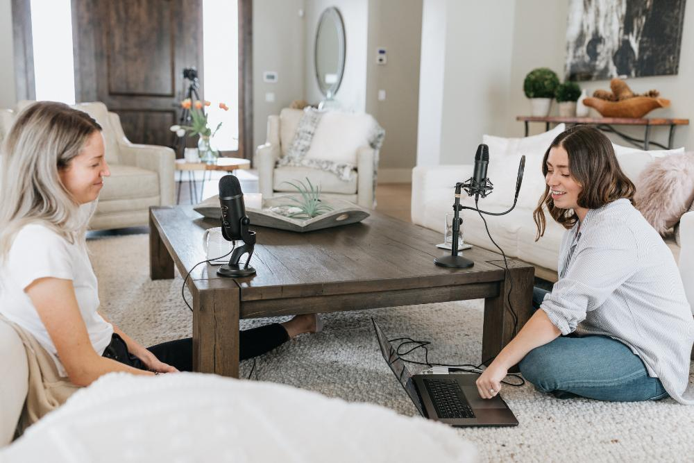 Two women record audio in livingroom