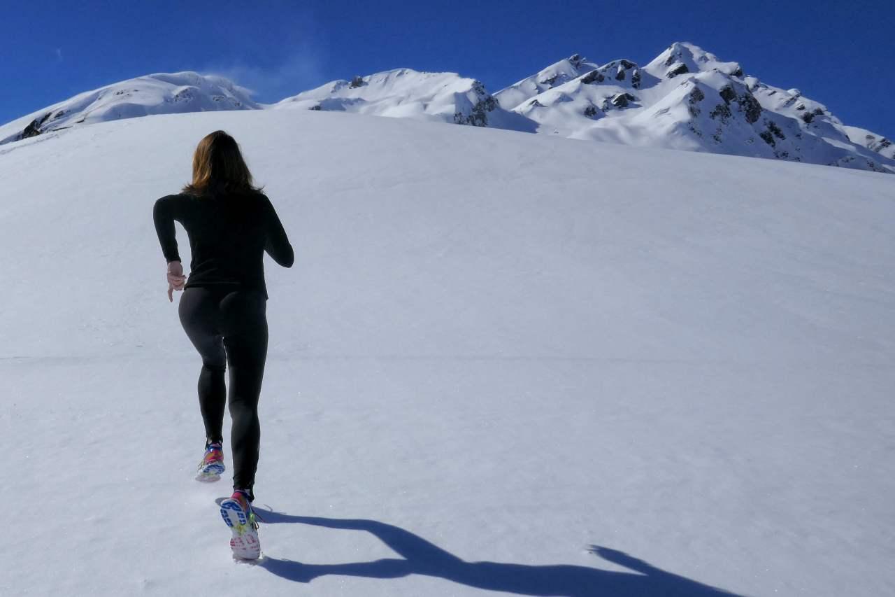 Woman running up a snowy hill